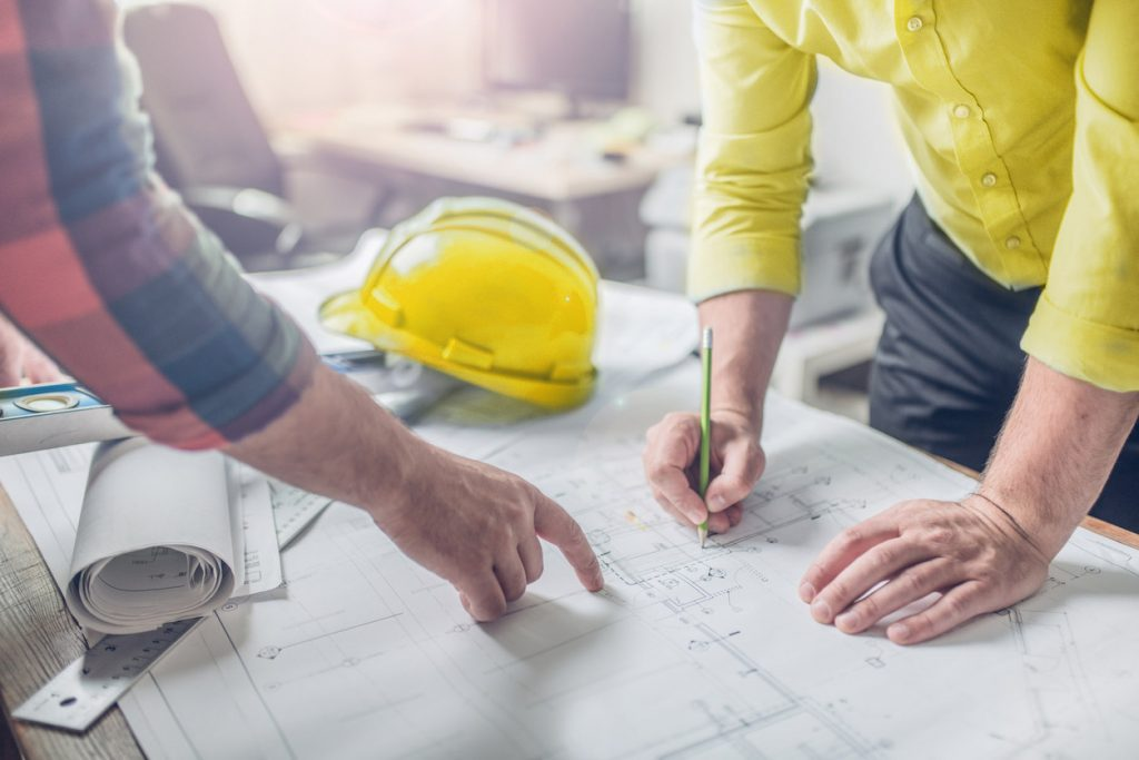 Architects and engineers make changes to construction blueprints.
